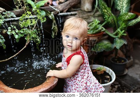 Little Girl With Blond Hair And Blue Eyes In Sundress Is Standing In Garden With Pot Plants And Wate