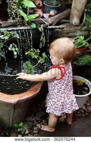 Little Girl With Blond Hair In Sundress Is Standing In Garden With Pot Plants And Waterfall And Play