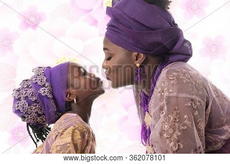Portrait In Profile Of A Mother And Child Girl Kissing. African Traditional Purple Clothing On Flowe