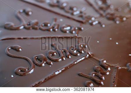 Closeup Chocolate Austrian Cake Sacher Sliced On White Table Background. Sacher Cake Slice. Traditio
