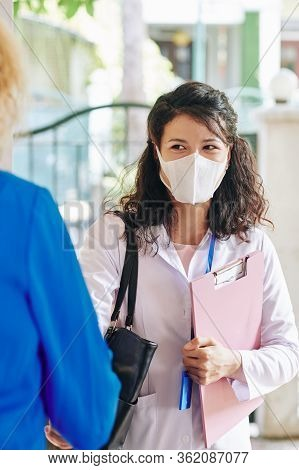Cheerful Young Doctor In Labcoat And Medical Mask Visiting Patient At Home