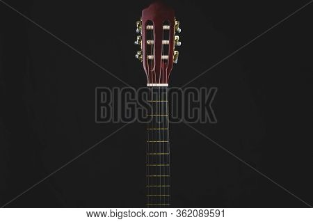 Guitar Fretboard On Black Background. Acoustic Musical Instrument. Copy Space