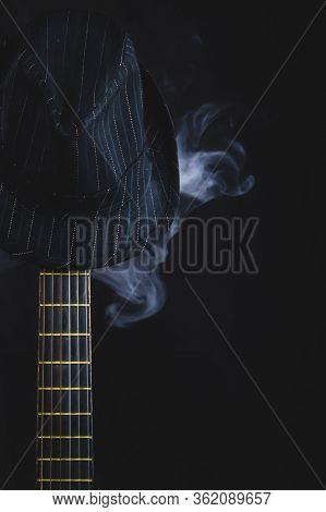 Smoking Hat Hangs On The Guitar Fretboard. Acoustic Musical Instrument. Strings On The Guitar Neck C