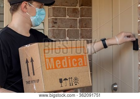 Contactless Delivery During Covid-19 Pandemic Lockdown Concept. Courier Wearing Mask And Gloves Hold
