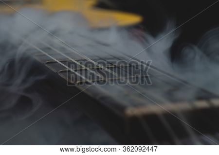 Acoustic Guitar In Smoke Close Up. Musical Instrument. Strings On The Guitar Fretboard