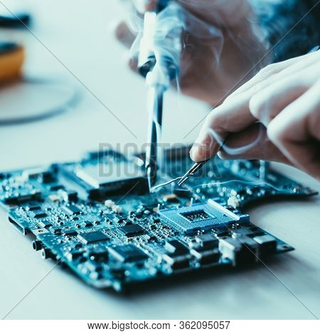 Electronic Engineering. Hardware Maintenance. Technician Soldering Motherboard.