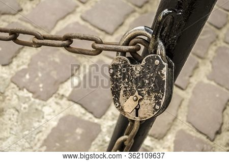 Padlock On A Chain On A Background Of Old Pavers. Old Town Photo .
