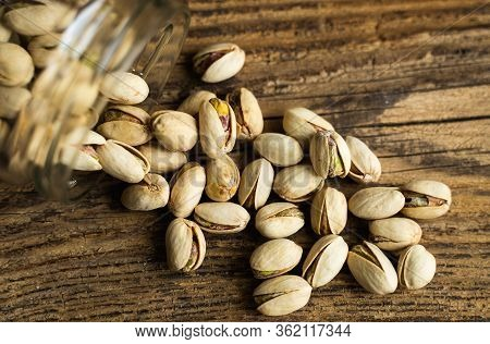 Pistachios Scattered On The Wooden Vintage Table From A Jar. Pistachio Is A Healthy Vegetarian Prote