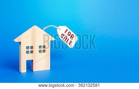 House Figure And For Sale Price Tag. Selling Real Estate, Lower Prices Because Of A Falling Market A