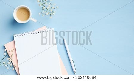 Flat Lay, Top View Feminine Workspace With Blank Notepad, Cup Of Coffee, Pen And Flowers On Blue Bac
