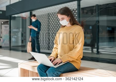 Female Blogger In A Protective Mask Works On A Laptop