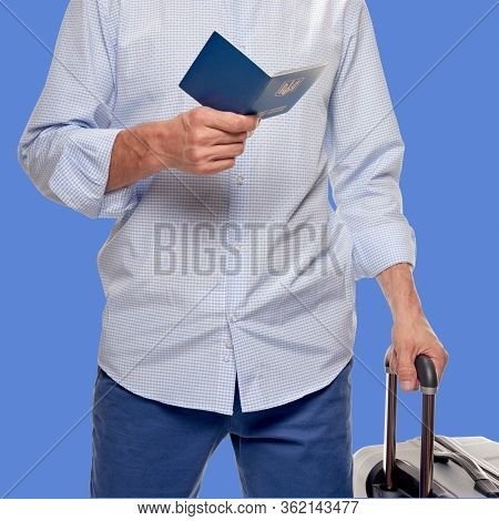 Part Of Man Tourist Holding Passport And Traveling With Visa-free Regime On Blue Cornflower Color Ba