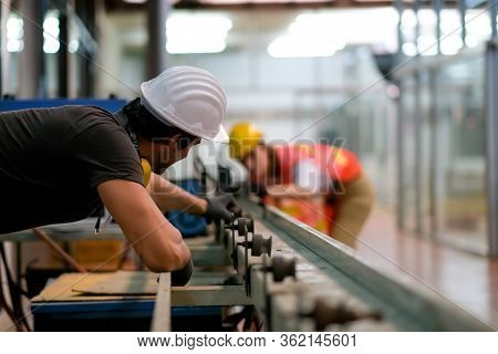 Technician Or Worker Or Engineer Man Look Through Rail Of Machine To His Co-worker In The Other Side