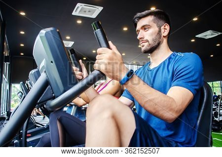 Portrait Of Young Man Exercising Using Stationary Bike In Gym With A Group Of People. Fitness Class