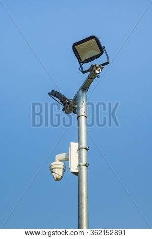 Security Camera And Floodlights Mounted On Mast Against A Blue Sky