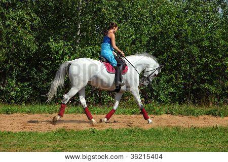 Girl horseback riding in the forest
