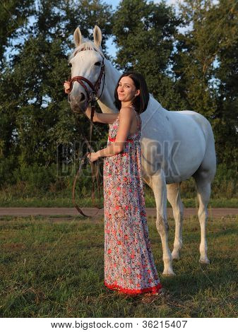 Pretty young girl together with her horse