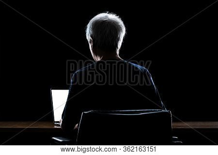 Back View Of A Man With Gray Hair Working From Home Late At Night Using His Laptop Computer, Back Li