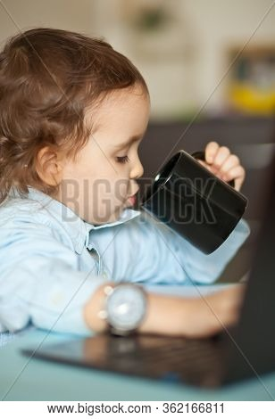 Workspace Office Desk With Laptop. Little Cute Business Girl Sitting At Table And Drinking A Mug Of