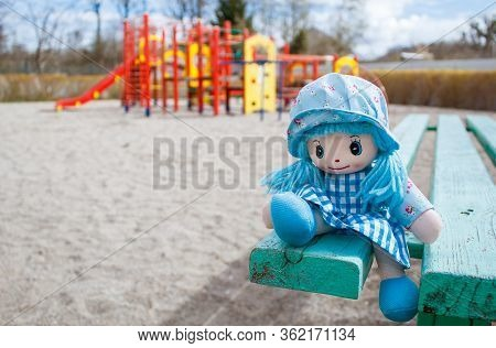 Forgotten Toy Doll Sitting On The Bench In The Empty Quarantined Playground On Sunny Spring Day