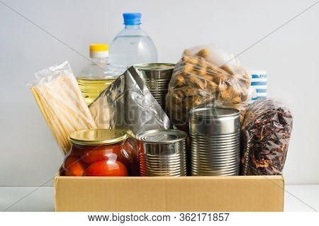Box For A Charity Donation With Food. Canned Food, Pasta, Pickled Tomatoes, Vegetable Oil, Water, Te