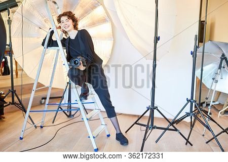 Confident photographer with camera leans against a ladder in the photo studio