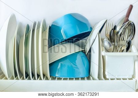 White And Blue Plates For Eating, Cutlery Forks, Knives, Spoons In A Glass For Drying Dishes In The