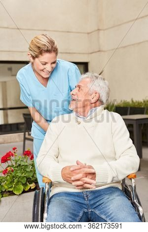 Nursing lady looks after a senior man in a wheelchair at the rehab clinic