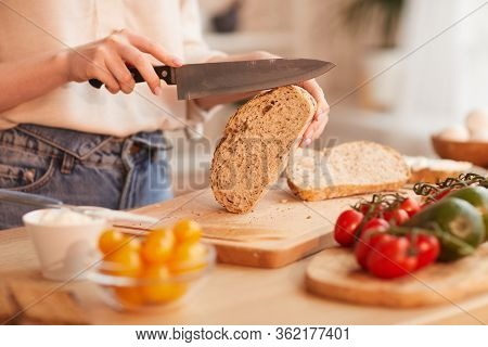 Warm-toned Close Up Of Unrecognizable Woman Cutting Fresh Wholewheat Bread While Making Breakfast In