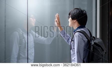 Young Asian Man Carrying Bag Looking At Himself Touching On Glass Window While Raining. Guy Reflecti