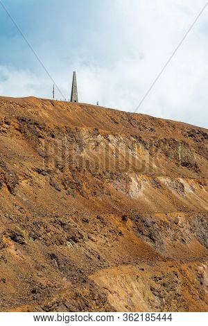 Dramatic View Of Distant Altitude Marking Obelisk On Top Of Red Mining Exploration Site Against Clou