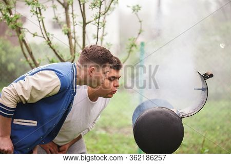 Two Young Men Standing Near Barbecue Grill. Kindling Of Fire In The Open Air.