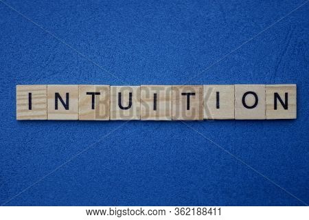 Text From The Gray Word Intuition From Wooden Small Letters On A Dark Blue Background