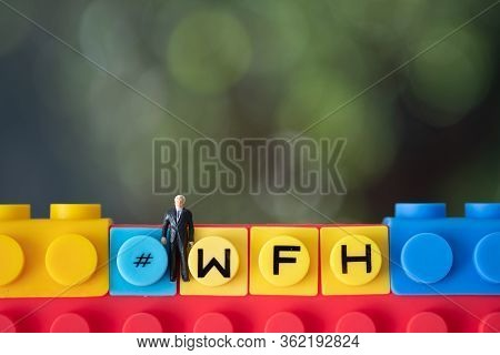 Miniature People With Hashtag Of Business Acronym Wfh As Work From Home And Miniature Office Table