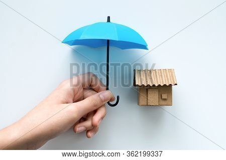House Insurance With A House Protected Under A Blue Umbrella As A Symbol Of Residential Security Fro