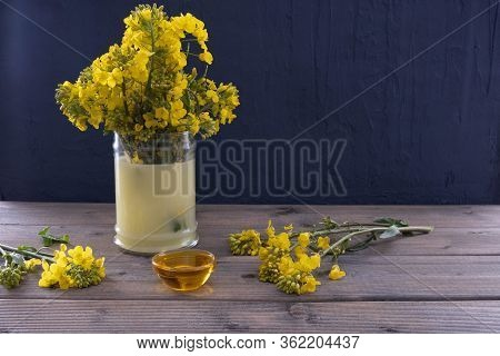 Canola Flowers Stand In A Vase, Near Canola Oil On A Wooden Table On A Blue Background
