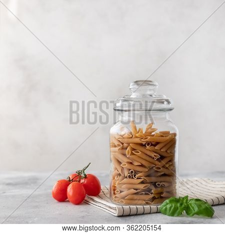 Wholewheat Penne Pasta In A Glass Container. Close-up. Diet Concept. Place For Text. Gray Background