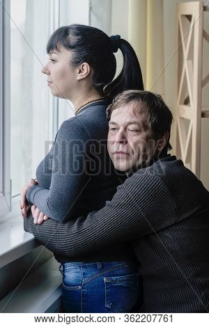 A Man Embraces A Woman Who Looks Out Of The Window. Perhaps They Are Lovers Or Husband And Wife, The
