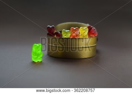 One Gummy Bear Stands Apart From A Group Of Other Jelly Bears Sharing The Same Candy Jar. Discrimina