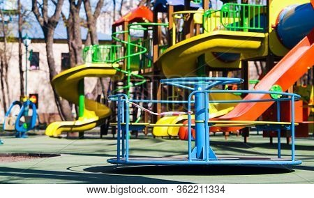 Carousel With Restriction Tape Spinning On Empty Playground In Public Park, Colorful Slides On Backg