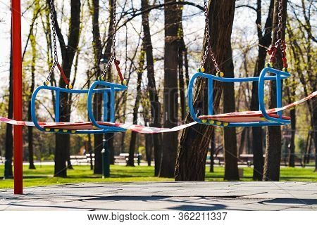 Restriction Red And White Tape On Swings On Empty Playground In Public Park, Trees On Background. St