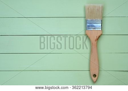 Paint Brush With Bristles And A Wooden Handle On A Green Background. Wooden Pale Green Boards Backgr