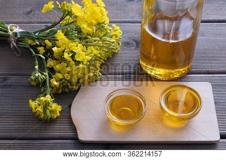 Small Cups With Rapeseed Oil And A Glass Bottle With Rapeseed Oil Next To Them Are Rapeseed Flowers