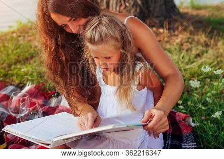 Mothers Day, Womens Day. Woman And Her Kids With Grandmother Reading Books. Family Having Picnic In