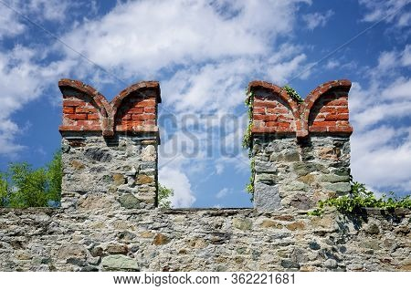 Castle Wall Merlons On A Fortified Wall In Italy With Swallowtail Shape And Clouds On The Background