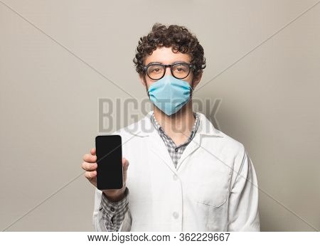 Doctor With Face Mask Holding A Cellphone