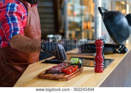 Chef salts steak before grilling in a restaurant