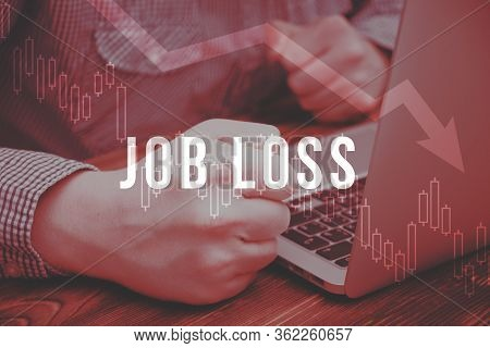 The Concept Of Job Loss On The Background Of A Man At A Laptop With Fists. Toned Red. Close Up.