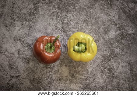 Red Bell And Yellow Bell Pepper On A Black Cement Background