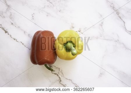 Red Bell And Yellow Bell Pepper On A White Marble Background